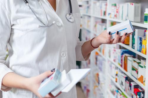 Woman pharmacist holding prescription checking medicine in pharm